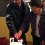 A former service user cuts the cake with Yvette Ball the Faith in Action chair
