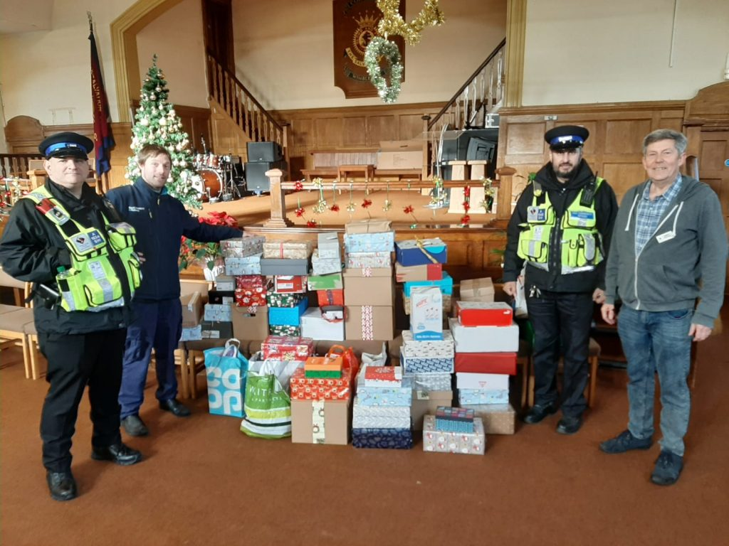 Manager Andy accepts donated shoeboxes filled with gifts from South Western Railway staff.